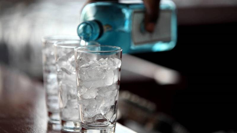 Garrafa de gin despejando a bebida em um copo com gelo