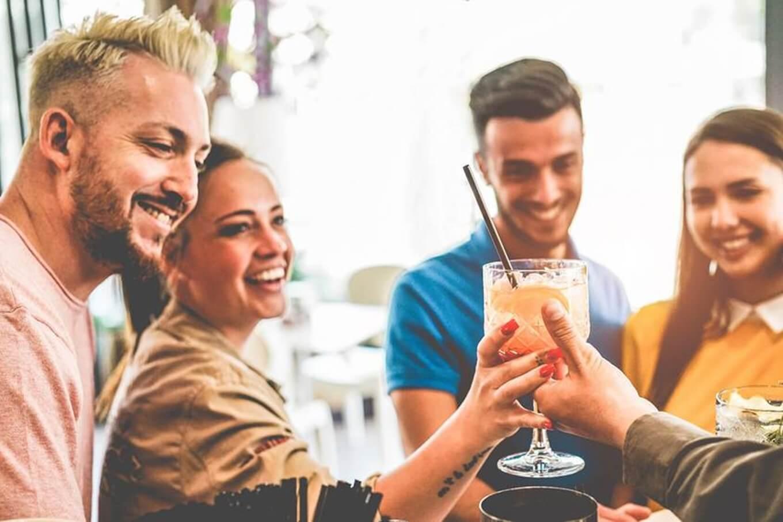 Gin sendo usado em brinde entre amigos contentes e sorridentes