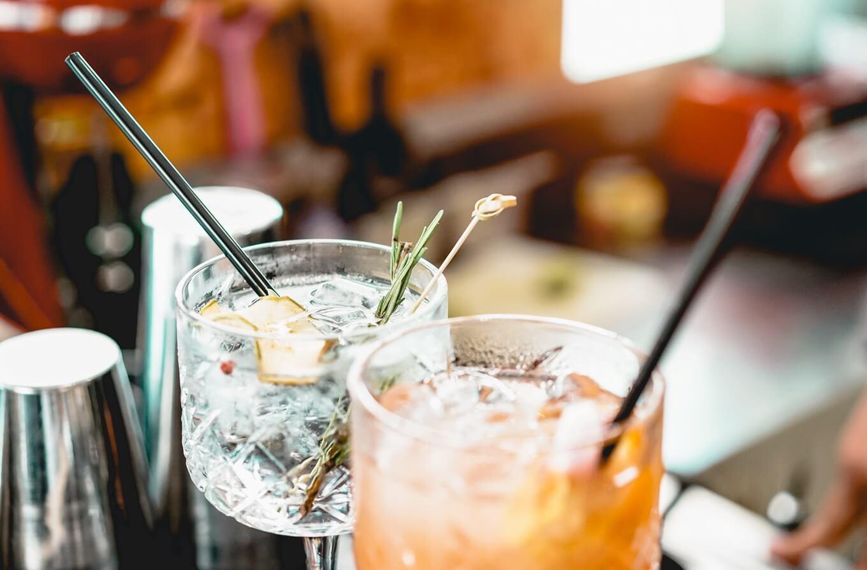 gin aromatizado com alecrim gelo com canudos pretos em ambiente alaranjado