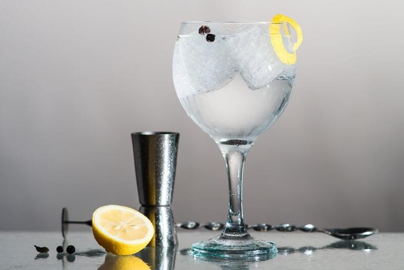 gin em taça com gelo, casca de limão com colher bailarina perto e dosador