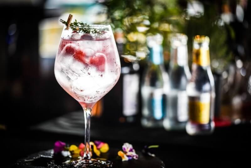 taça alta com gin, gelo, ervas aromáticas, flores no pé da taça e ao fundo várias garrafinhas de agua tônica
