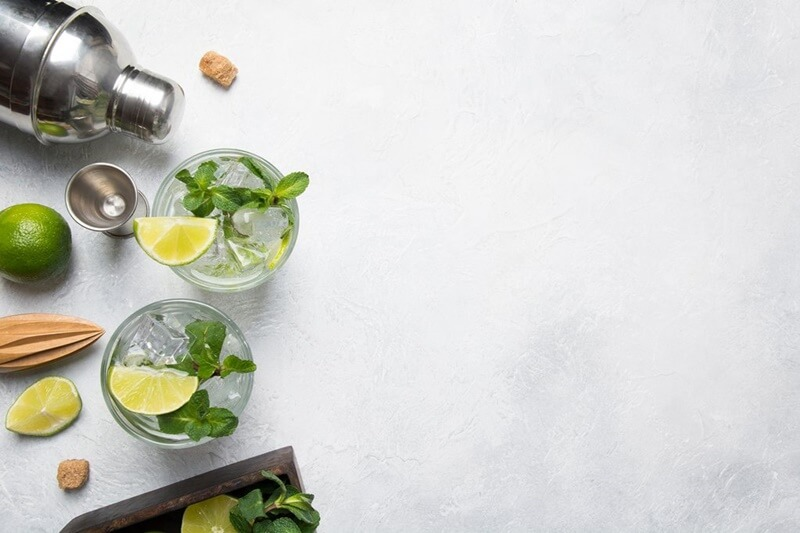bancada com coqueteleira, limão inteiro, fatias de limão, espremedor de limão de mão, ervas aromáticas e copos de vidro