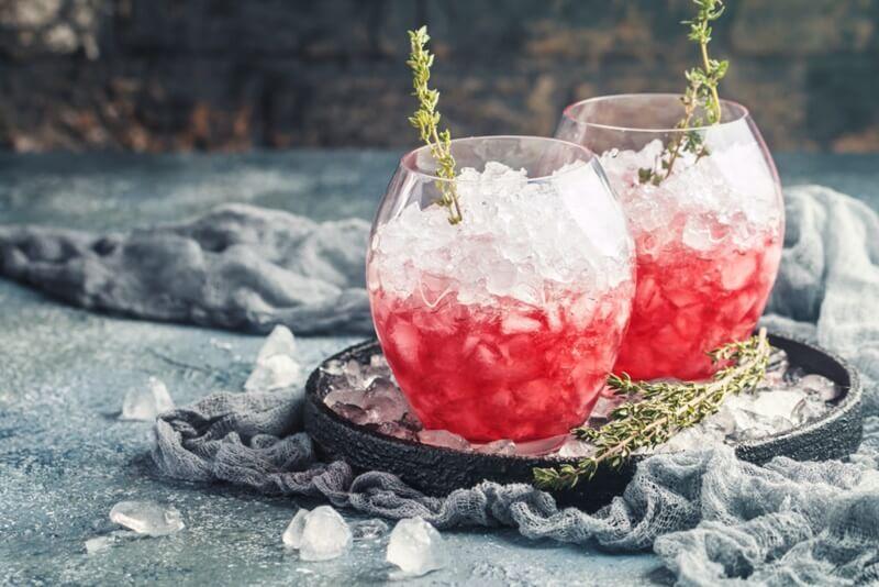 gin servido com muito gelo bem picado com geleia de morango aromatizado com ramo de erva, gin tônica com geleia de morango