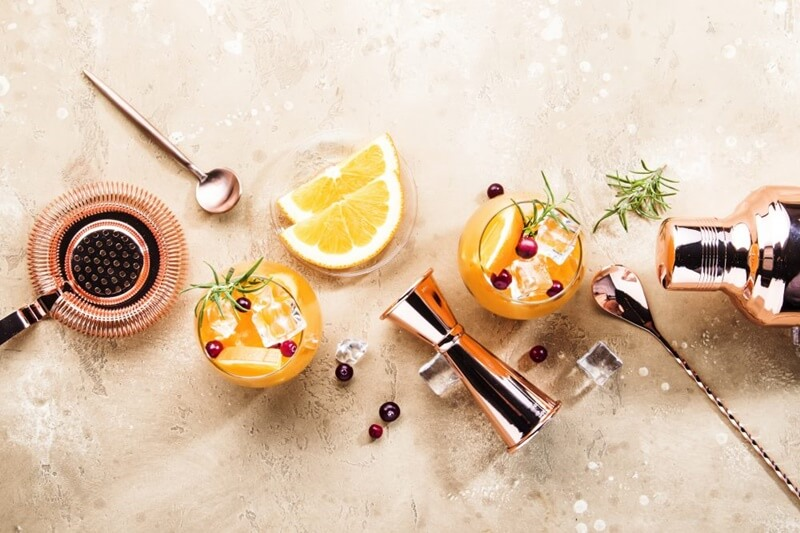 mesa com colher bailarina, fatias de laranja, ramos de alecrim, pimenta rosa