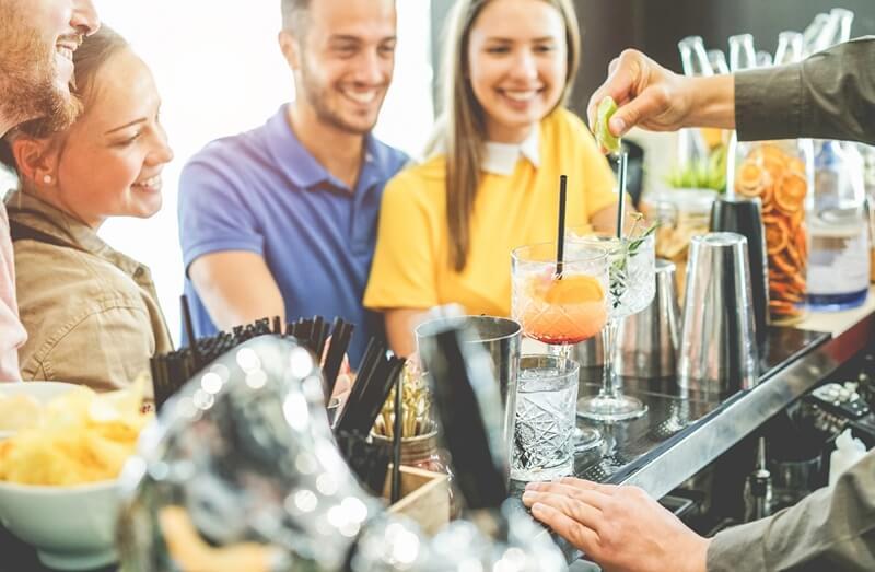 melhores drinks com gin 2020 sendo bebido pela galera no bar vendo a preparação do drink, muitos sorrisos, canudos pretos, fatias de cítricos ao fundo e balcão preto