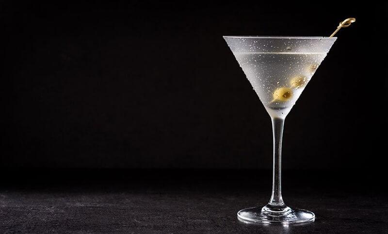 Dry Martini em taça longa com azeitonas espetadas em fundo escuro